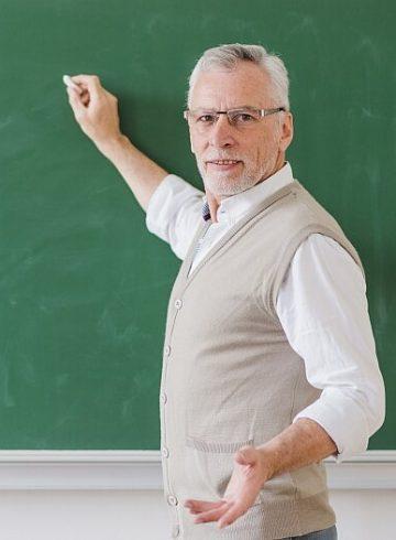 Doświadczony nauczyciel w szkole pisze na tablicy